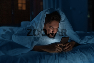 indian man with smartphone in bed at home at night