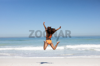 Mixed race woman jumping on the beach