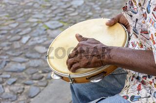 Samba performance with musician hands playing tambourine on Salvador city streets