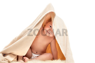 small child plays under beige towel