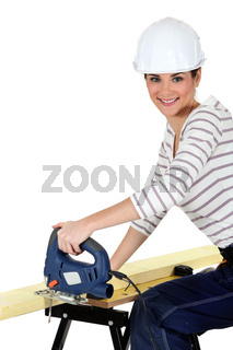 Woman cutting wood with a jigsaw