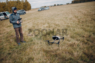 Man pilot controlling quadcopter drone with remote controller pad