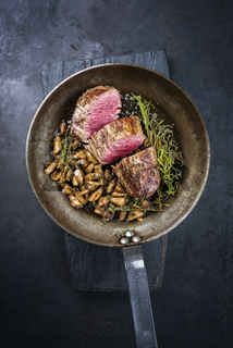 Fried dry aged beef fillet steak natural with king trumpet mushroom and herbs offered as top view in a rustic frying pan