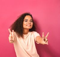 Happy sending PEACE gesture with two hands beautiful young African American woman looking positively at camera wearing peachy t-shirt isolated on pink background. Beauty concept. Square crop