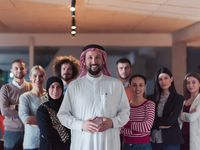 Portrait of multiracial diverse group of businesspeople team standing behind older Arab team leader
