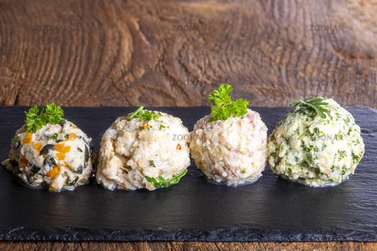 four different dumplings on slate