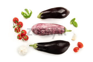 A flat lay composition with vegetables. Eggplants, tomatoes, basil leaves and garlic