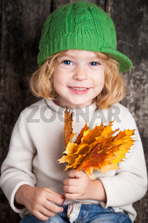 Kid with yellow maple leaves