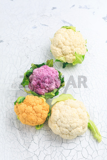 Organic colorful cauliflower on old kitchen table