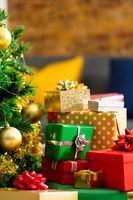 Composition of christmas tree and stacked presents on blurred background