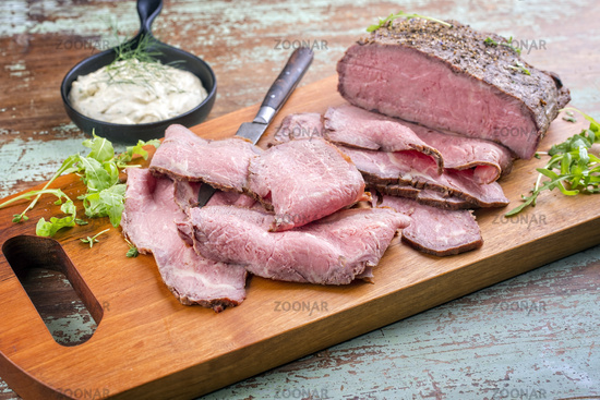 Modern style traditional lunch meat with sliced cold cuts roast beef with rocket salad and remoulade offered as top view on a wooden design board