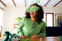 Caucasian woman dressed in green with shamrock glasses for st patrick's day laughing