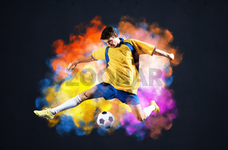 Soccer player kicking ball in colorful smoke