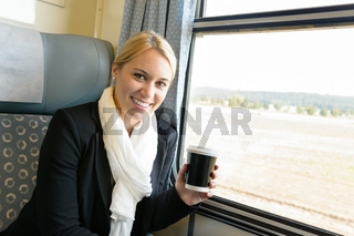 Woman smiling sitting in train holding coffee