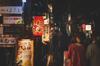 Tourists walking along restaurants and bars in Pontocho street at night in old town of Kyoto, Japan