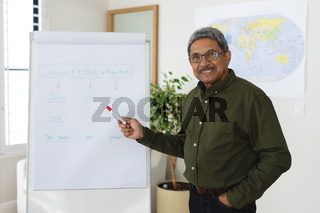 Mixed race male english teacher standing at a whiteboard giving an online lesson to camera