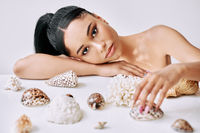Closeup portrait of beautiful african american woman with different seashells on white background