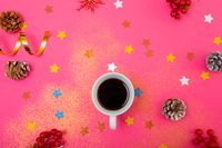 Composition of christmas decorations with pine cones, stars and coffee on pink background