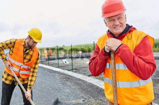 Älterer Bauarbeiter und ein Kollege schaufeln Beton