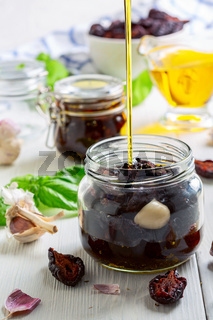 Preparation of dried plums with Italian herbs and olive oil.