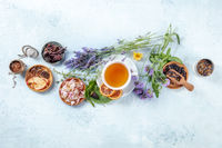 Organic tea. Herbs, flowers and fruit around a cup of tea, a flat lay, top shot