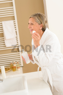 Mature woman bathroom clean face make-up removal