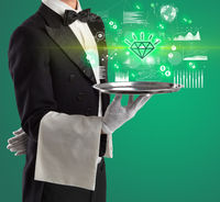 Handsome young waiter in tuxedo holding currency icons on tray