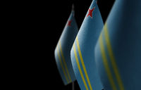 Small national flags of the Aruba on a black background