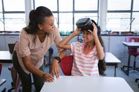 African american female teacher teaching a girl to use vr headset in the class at school