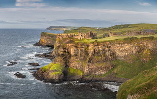 Panoramic shot of Dunluce Castle at sunset located on the edge of cliff, Northern Ireland