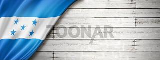 Honduras flag on old white wall banner