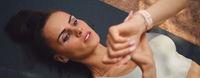 Woman lying on mat looks at wristwatch start sport training