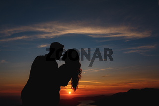 Silhouettes of the bride and groom who are embracing and kissing on Mount Lovcen overlooking the Bay of Kotor at sunset