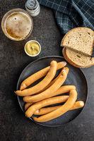Smoked frankfurter sausages on plate.