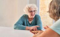 Fröhliche Seniorin hat Spaß beim Damespiel Wettkampf