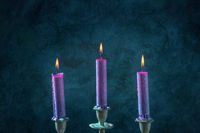 Candle magic. Purple candles burning on a dark blue background