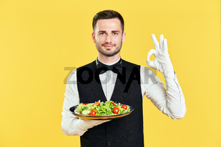 Happy smiling waiter holding plate with healthy vegetable salad doing ok sign with hand and fingers on yellow background
