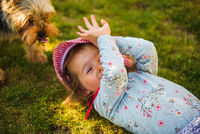 Baby girl lying on grass with dog in backyard on summer day.