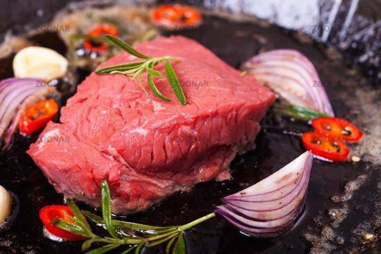 raw steak in an iron pan
