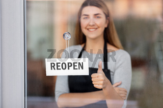 woman with reopen banner on door showing thumbs up