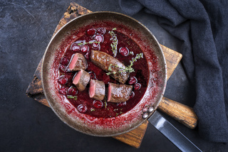 Traditional wild hare back filet braised with wild berries and cherry relish souse served as top view in rustic frying pan on an old wooden board