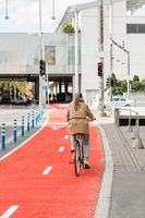 woman cycling along red bike lane road in city