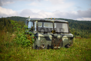 Abandoned vehicle among nature. Summer sunny day in mountains