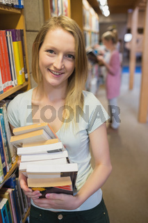 Student standing at a bookshelf at the library holding books