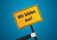 Yellow sign with German text meaning we train employees