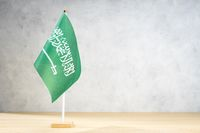 Saudi Arabia table flag on white textured wall. Copy space for text, designs or drawings
