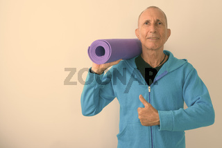 Studio shot of happy bald senior man holding yoga mat and giving thumb up ready for gym