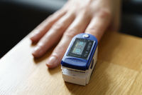 Middle age woman at home checking blood oxygen level with pulse oximeter. Coronavirus covid symptoms. Asthma, lungs decease.