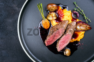 Modern style traditional wild hare back filet braised with wild berries and red wine jus with mashed carrot puree and sweet potato served as top view on Nordic design plate with copy space left