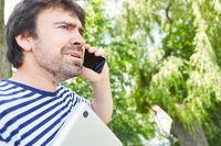 Mann als Freelancer telefoniert mit dem Smartphone